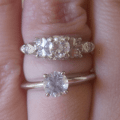 Diamond ring on top and white sapphire ring below