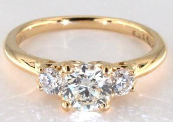 0.99ct K colored SI1 diamond on a three-stone yellow gold ring setting